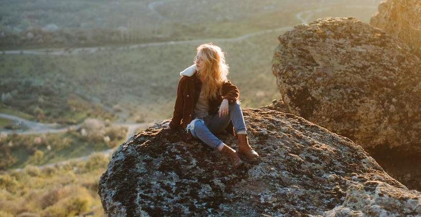 a woman hiking and sitting on the mountain top on the Tweed Coast national park