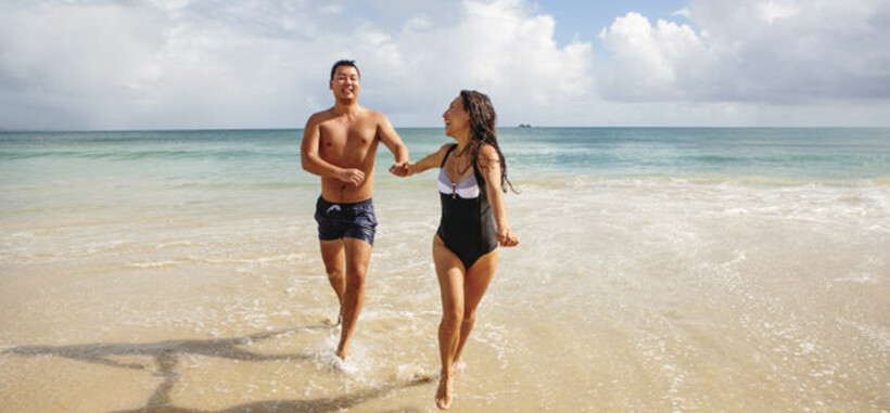 a couple running in the water at Clarkes Beach in Byron Bay