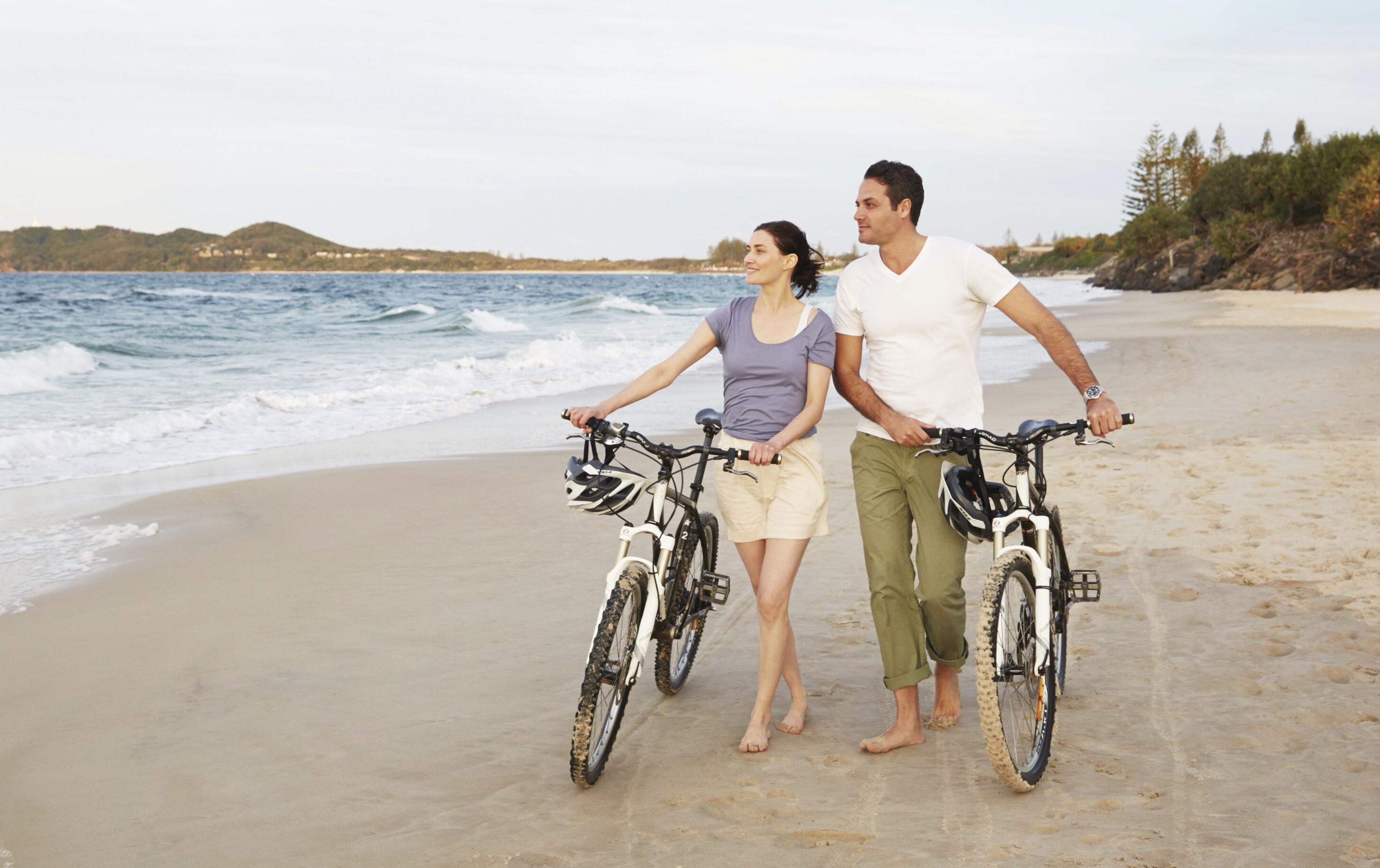 a couple walking with their bikes on the sand on the Byron Bay beach