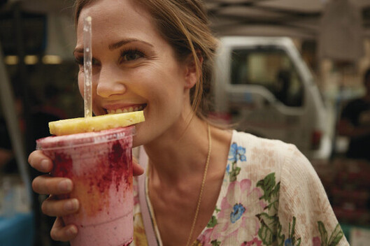 a woman enjoying a delicious smoothy at Rusty Markets in Cairns