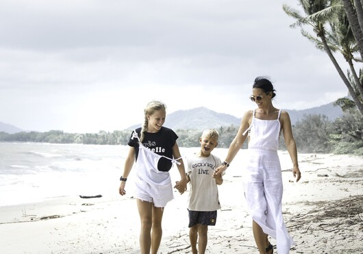 a mother and her 2 children walking along the Palm Cove beach