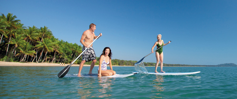 people Stand-up Paddleboarding at one of the beaches around Cairns
