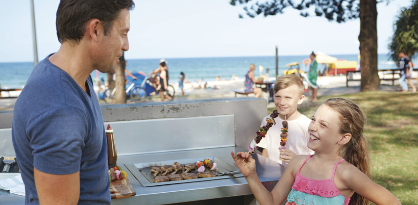 a dad cooking dinner at one of the free BBQs and laughing with his daughter at a Gold Coast beach