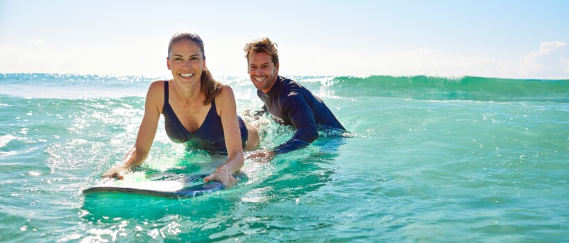 A woman lying on a surfboard learning to surf, and the instructor is at the back of the board giving the board a push