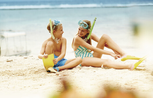 2 children futting their fins on to go snorkelling on the Great Barrier Reef