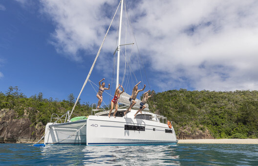 people jumping off a sailing boat into the clear blue water in the Whitsundays