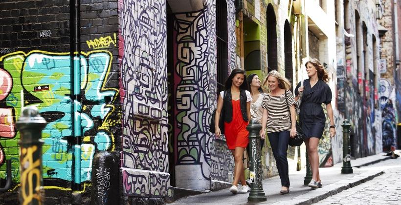 a group of friends walking through Melbourne's laneways and enjoying the abundance of street art