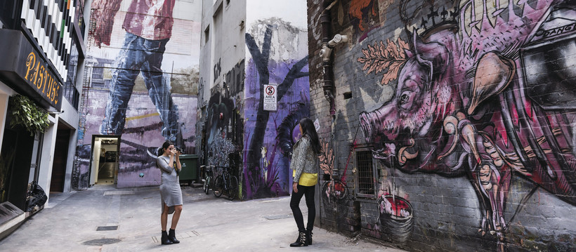 Friends taking photos of each other in Melbourne's Duckboard Place laneway
