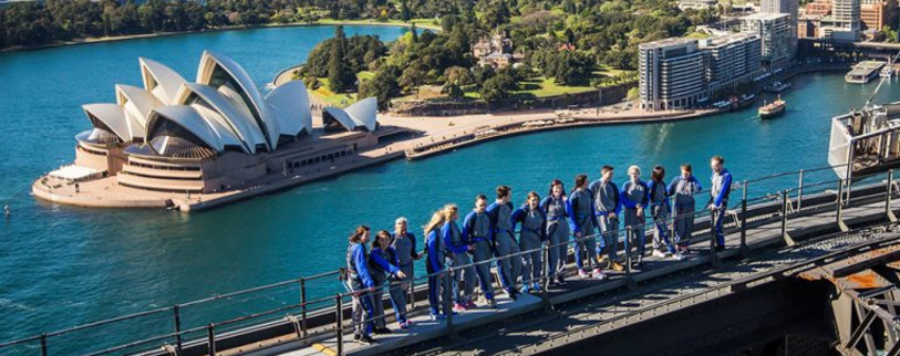 Group of people at the top of the Sydney Harbour Bridge after doing a BridgeClimb
