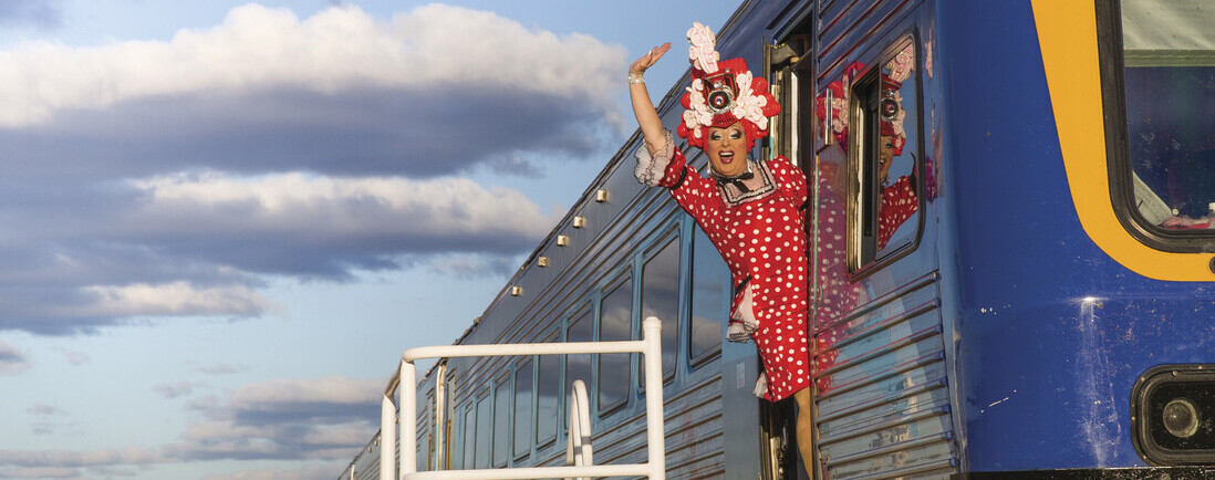 A drag queen waving from the train as it pulls into Broken Hill for the Broken Heel Festival.