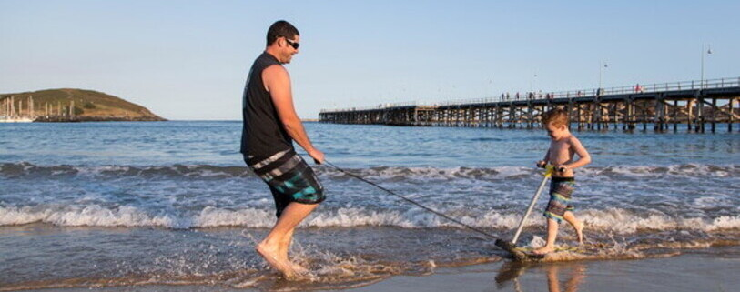 a dad and his son playing in the water at Coffs Harbour jetty beach