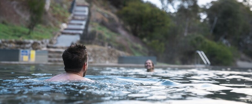 a couple having a dip in the Kosciuszko National Park Yarrangobilly Caves thermal pool.