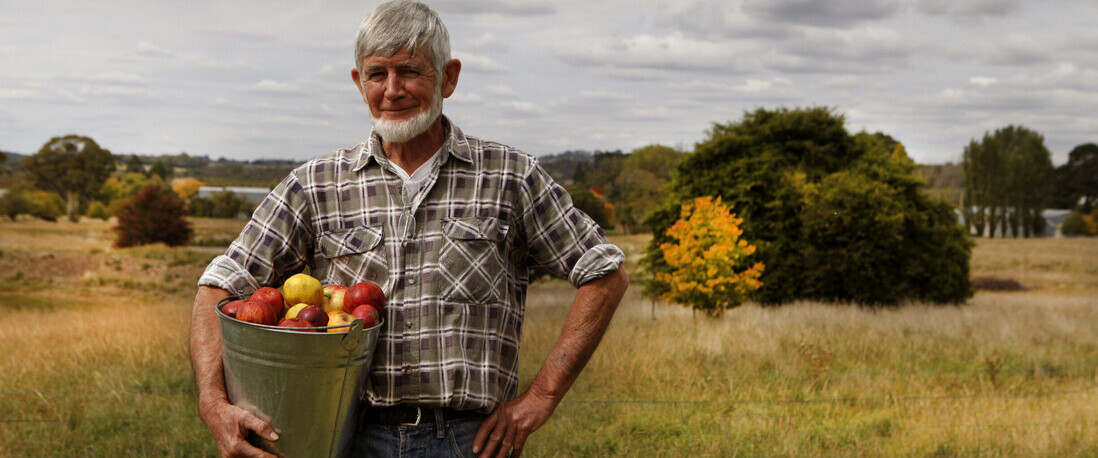 A man holding a bucket of apple atSmall Acres Cyder brewery in Orange.