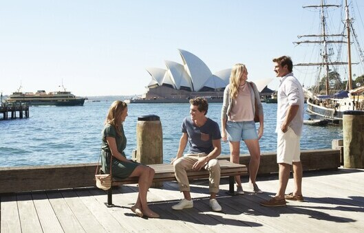 four friends relaxing and chatting at Circular Quay with the Sydney Opera House in the background