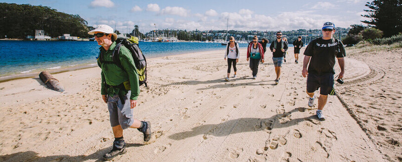 A group of people walking along the beach, as part of the Manly to Spit Bridge walk.