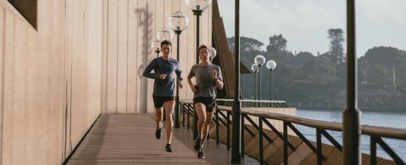 two people running around the Opera House foreshore