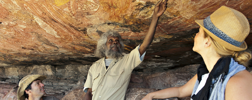 a local indigenous guide showing people Aboriginal Rock art in caves in the Northern Territory