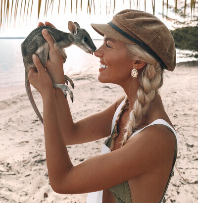 a woman cuddling ababy wallaby on the beach at Tiwi Island Retreat