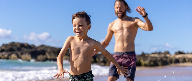 a dad and his son running and playing on the beach