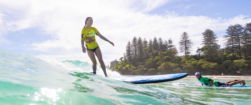 A young girl learning to surf with 'Walk on Water surf lesson' at Greenmount beach on the Gold Coast.