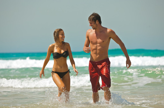 a man and woman walking out of the surf on a Gold Coast beach