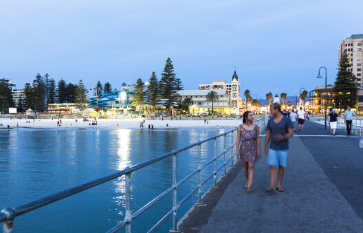 A couple strolling along the jetty at Glenelg in Adelaide