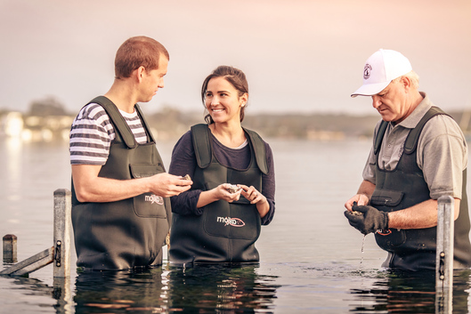 a couple learning to shuck oysters at Coffin Bay