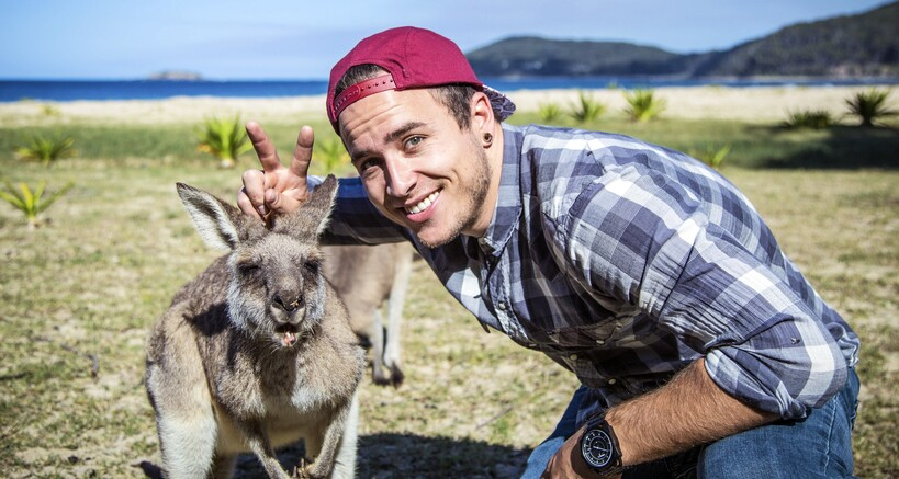 a man with one of the local kangaroos at Pebbly Beach at Murramarang national park in the Shoalhaven
