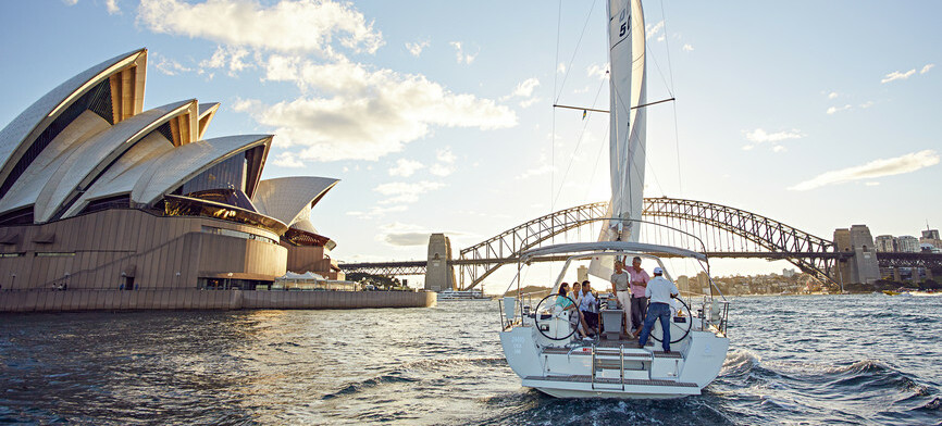 People on a sailing boat going past the Sydney Opera House and heading towards the Harbour Bridge