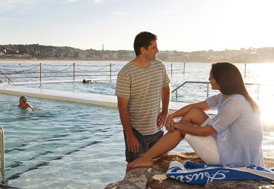 A couple sitting on the edge of the Bondi Icebergs ocean pool in Sydney