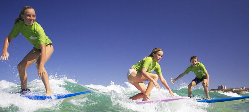 kids learning to surf and catching waves on Bronte beach in Sydney