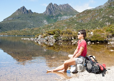 a woman sitting on a rock and soaking her feet in the river at Cradle Mountain