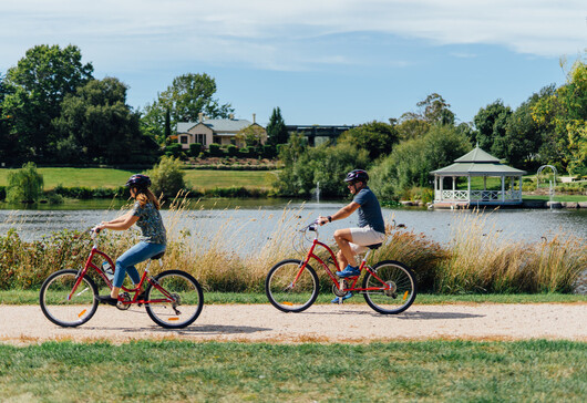 a man and woman cycling around the Josef Chromy vineyards