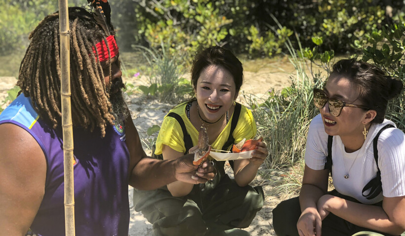 People enjoying a pot-to-plate adventure with local Aboriginal tour guide - 'The Black Cockatoo' when they booked aTweed Cruise