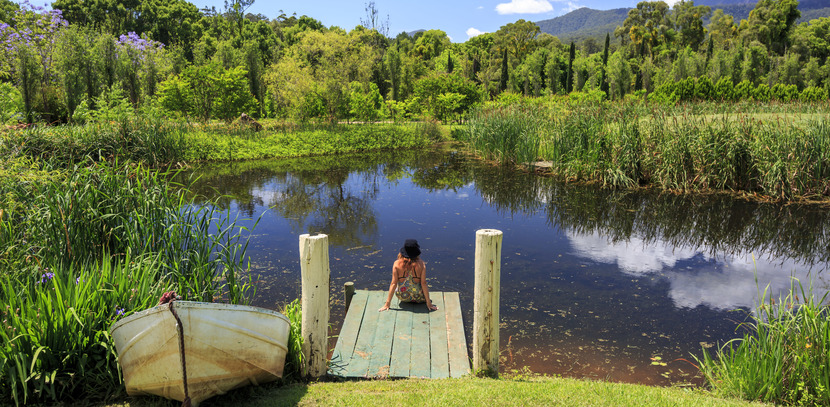 A woman sitting on the wharf and admiring the Tweed Coast mountains