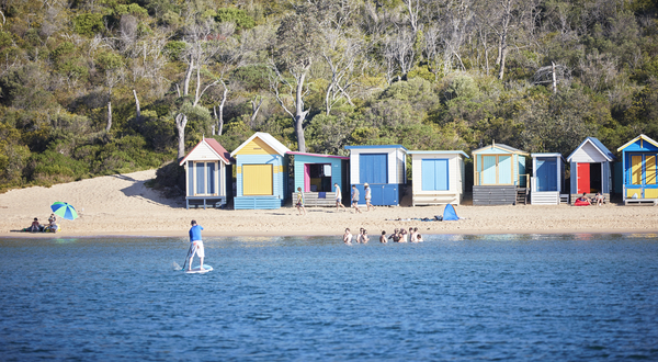 The beach huts and people enjoying the water at one of the seaside towns on the Mornington Peninsula.