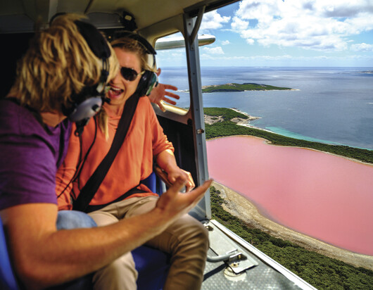 a couple in an aeroplane flying over the amazing Pink Lake (also known asLake Hillier)