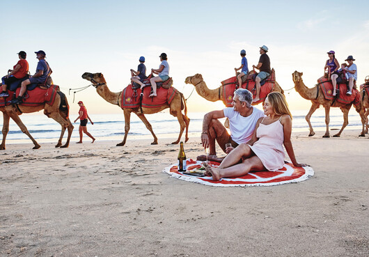 A couple sitting on the beach watching the camel train go past on Cable Beach in Broome