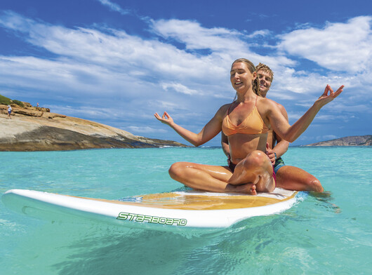 A couple sitting on a surfboard in the turquoise waters at Esperance beach