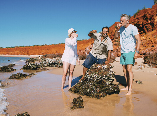 A couple eating fresh oysters straight off the rock at Francois Peron National Park.