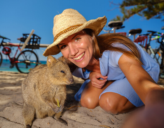 A woman taking a selfie with a Quokka on Rottnest Island