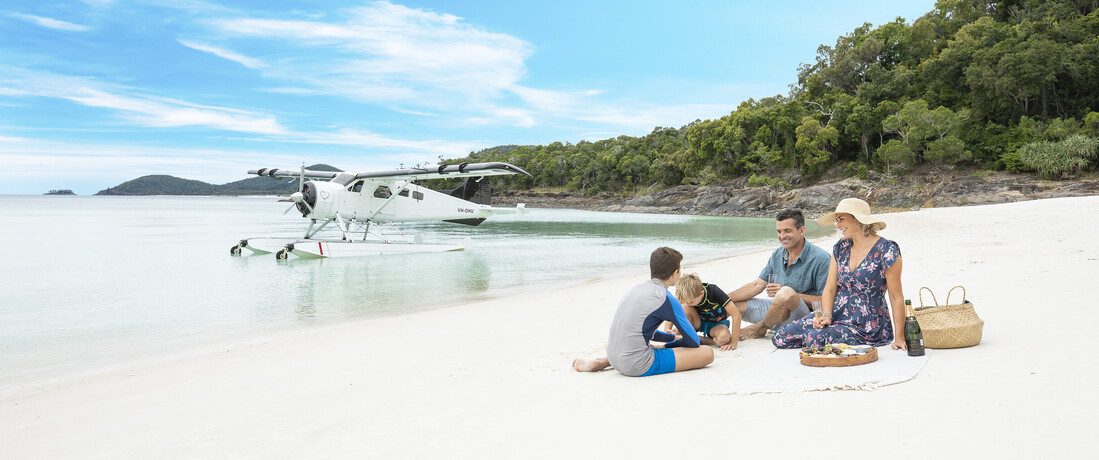 a family picnicking on Whitehaven Beach in the Whitsundays with a seaplane behind them